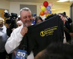 Ricky Davis holds up a shirt with the logo of the Innocence Project after he was released from custody at the El Dorado County Jail in Placerville, Calif., Thursday, Feb. 13, 2020