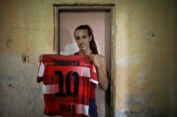 Soccer player Mara Gomez poses with her old jersey from the first amateur soccer club she played for, Toronto, in La Plata, Argentina.