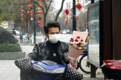 A man wearing a face mask carries a Valentine's Day bouquet as he rides a scooter in Hangzhou in eastern China's Zhejiang Province.