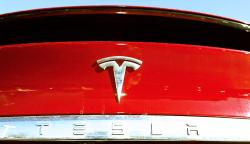 In this Feb. 2, 2020 file photograph, the company logo sits on an unsold 2020 Model X at a Tesla dealership in Littleton, Colo.