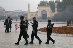 In this Nov. 4, 2017, file photo, Uighur security personnel patrol near the Id Kah Mosque in Kashgar in western China's Xinjiang region