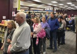 People wait in line for at an early caucus site at the Sparks Library, Saturday, Feb. 15, 2020 in Sparks, Nev.