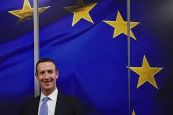 Facebook CEO Mark Zuckerberg smiles as he shakes hands with European Commissioner for Values and Transparency Vera Jourova prior to a meeting at EU headquarters in Brussels, Monday, Feb. 17, 2020