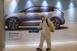 In this Feb. 12, 2020, photo, a worker disinfects a mall near an advertisement for a car in Beijing, China