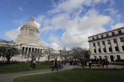 People gather at the sundial in front of the Legislative Building, left, at the Capitol in Olympia, Wash.