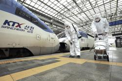 Workers wearing protective gears spray disinfectant as a precaution against the new coronavirus at Seoul Railway Station in Seoul, South Korea.