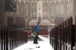 A worker wearing a face mask sprays disinfectant as a precaution against the coronavirus at Myeongdong Cathedral in Seoul, South Korea.