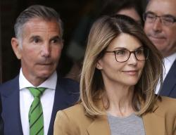 Actress Lori Loughlin, front, and her husband, clothing designer Mossimo Giannulli, left, depart federal court in Boston.