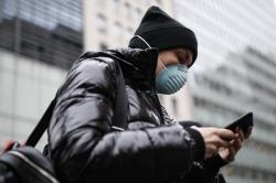 Pedestrian uses her phone while wearing a face mask in Herald Square, Thursday, March 12, 2020, in New York