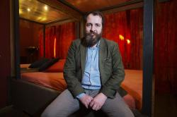 Aurel Johannes Marx sits on a bed in his three room brothel 'Lankwitzer 7' as he poses for photo after and interview with the Associated Press in Berlin.