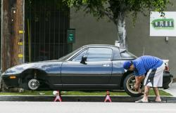 In this Sept. 10, 2015, file photo, a man repairs one of the two tires that he said blew up suddenly while driving on Interstate 5 in Los Angeles.