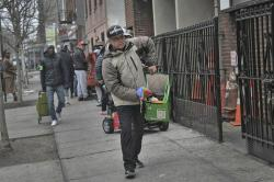 Jose Rosa, 63, moves forward in the queue where he waits to collect food donations from St. Stephen Outreach in the Brooklyn borough of New York, on Friday, March 20, 2020