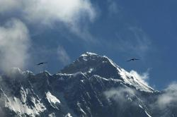 In this May 27, 2019, file photo, birds fly as Mount Everest is seen from Namche Bajar, Solukhumbu district, Nepal