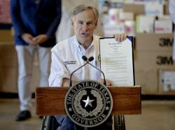 Texas Gov. Greg Abbott shows a new executive order regarding reporting data about the coronavirus during a news conference on Tuesday, March 24, 2020, in Austin, Texas