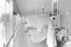 In this November 1918 photo made available by the Library of Congress, a nurse takes the pulse of a patient in the influenza ward of the Walter Reed hospital in Washington.
