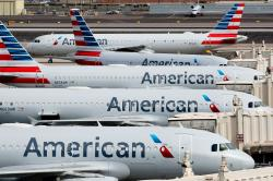 In this Wednesday, March 25, 2020 file photo, American Airlines jets sit idly at their gates as a jet arrives at Sky Harbor International Airport in Phoenix