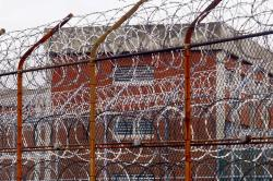 In this March 16, 2011, file photo, a security fence surrounds inmate housing on the Rikers Island correctional facility in New York.