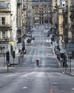 A cyclist makes his way up a quiet Saint Vincent Street as the UK continues in lockdown to help curb the spread of the coronavirus, in Glasgow, Scotland
