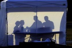 In this Wednesday, March 25, 2020 file photo, medical personnel are silhouetted against the back of a tent before the start of coronavirus testing in the parking lot outside of Raymond James Stadium in Tampa, Fla.