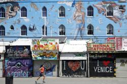 A man jogs in front of closed-off store fronts in Venice Beach.