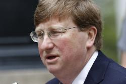 In this Tuesday, March 24, 2020, file photo, Mississippi Republican Gov. Tate Reeves speaks with reporters outside the Governor's Mansion to give an update on the current situation of the new coronavirus in the state and discuss Mississippi's ongoing response to slow the spread, in Jackson, Miss.