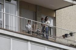 In this March 19, 2020, file photo, people look out from their balcony in Madrid, Spain