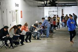 In this March 13, 2020 file photo, unionized hospitality workers wait in line in a basement garage to apply for unemployment benefits at the Hospitality Training Academy in Los Angeles