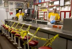 Texas Tavern employees Chris Dobe, left, and Nick Moore wait for take out orders on Monday night, March 30, 2020