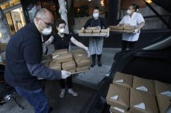 Nightbird Restaurant general manager Ron Boyd, from left, pastry chef Hope Waggoner, chef and owner Kim Alter and sous chef Bailey Walton pack dinner boxes into Alter's car that were delivered to hospital workers in San Francisco.