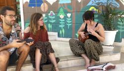 Canadian tourist Lambert Desrosiers Gaudette, left and British tourist Emma Snashford,listen as another stranded foreign tourist plays ukulele at a hostel in New Delhi, India.