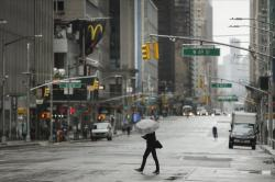 A pedestrian crosses the street in NYC.
