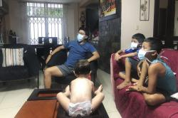In this March 26, 2020, photo, relatives of Bella Lamilla the first person to be diagnosed with coronavirus in Ecuador, maintain quarantine in their home in Babahoyo, Ecuador