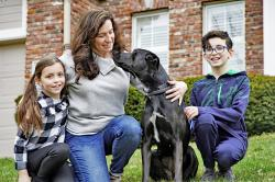 In this March 27, 2020 photo, Kim Simeon and children Annabel, 9, and Brennan, 11, pose for a photo with Nala, a dog they are fostering, in Omaha, Neb.