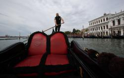 In this picture taken on Wednesday, May 13, 2020, gondoliers President Andrea Balbi sails his gondola at the canal Grande (Grand Canal) in Venice, Italy