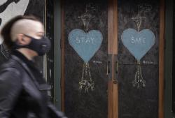 A pedestrian wearing a face mask walks past art by the street artist @dozfy, featuring the Space Needle on the boarded-up Virginia Inn Restaurant and Bar, Saturday, May 16, 2020, in downtown Seattle.