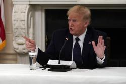 President Donald Trump tells reporters that he is taking zinc and hydroxychloroquine during a meeting with restaurant industry executives about the coronavirus response, in the State Dining Room of the White House.