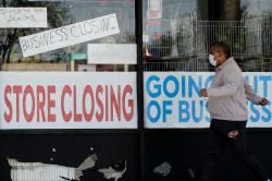 A man looks at signs of a closed store due to COVID-19 in Niles, Ill., Thursday, May 21, 2020