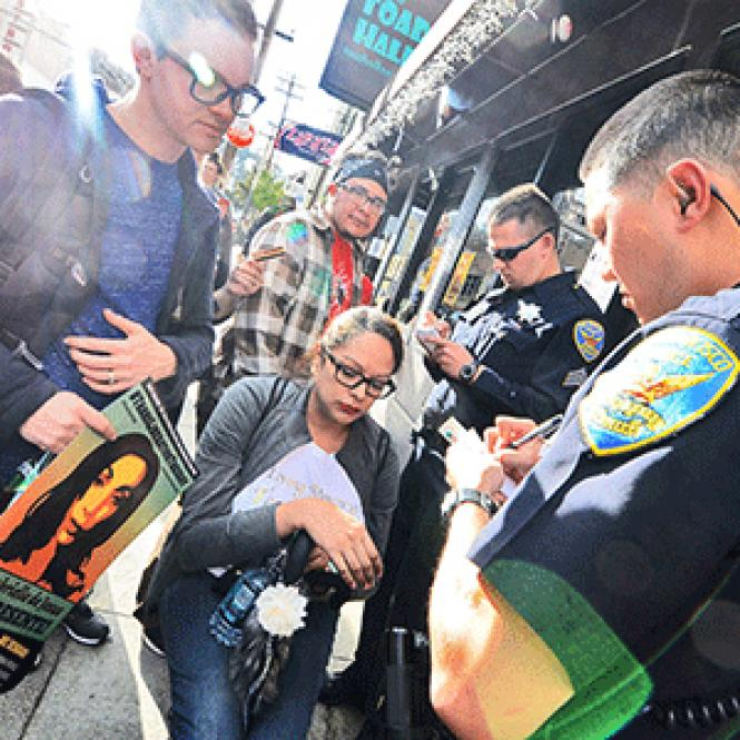 San Francisco Police Officer C. Stokes, right, takes a report from Danielle Castro, seated center, who said she was battered by an employee of Toad Hall as he was trying to close the door to the bar