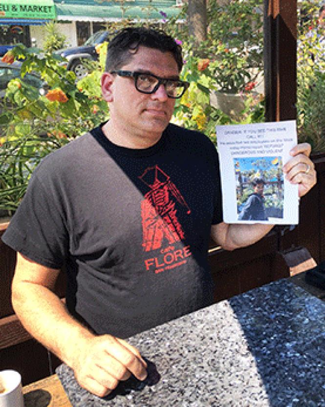Cafe Flore owner Stu Gerry holds a flier warning customers about a man who had reportedly caused problems at the eatery