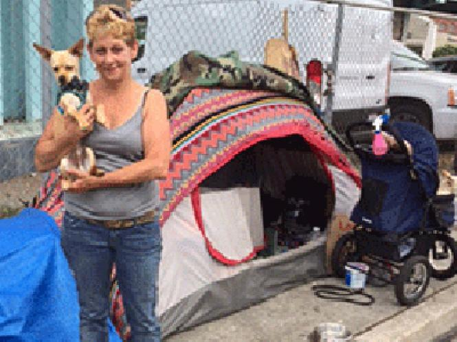 Toni Machado stands outside her tent with Peanut Butter, her rat terrier