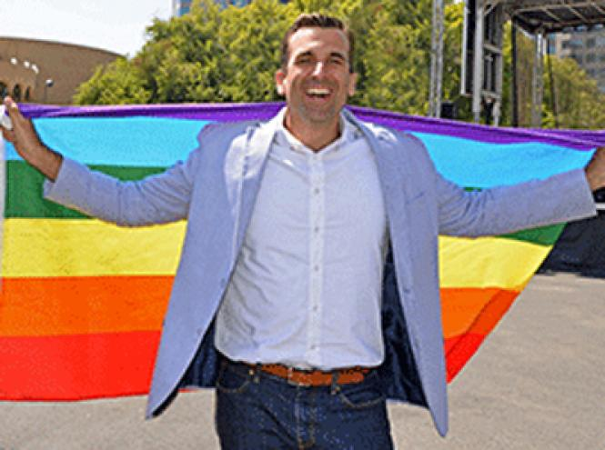 San Jose Mayor Sam Liccardo, who recently announced he is running for re-election, draped a rainbow flag over his shoulders at last year's Silicon Valley Pride
