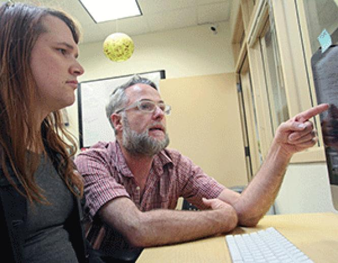 Q Foundation Executive Director Brian Basinger,<br>right, discusses job performance statistics with peer navigator Nicole Dunn,<br>left, at the Q Foundation office March 30 Photo: Erin Lefevre<br><br><br><br><br><br><br><br><br><br><br><br>
