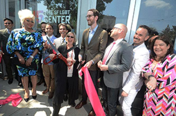 Executive Director Rebecca Rolfe holds oversize scissors<br>and state Senator Scott Wiener holds the ribbon as people cheer at the April 9<br>reopening of the San Francisco LGBT Community Center. Photo: Rick Gerharter