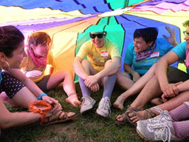 Queer Camp participants sit under a parachute in 2013.<br>Photo: Claire Woods
