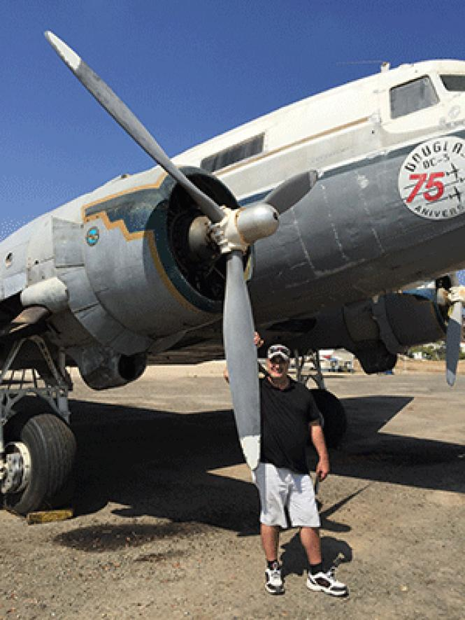 Denis James &quot;DJ&quot; Dorn stands next to the DC-3<br>plane he hopes to purchase for his Pride Flight around the world. Photo:<br>Courtesy Pride Flight 2018