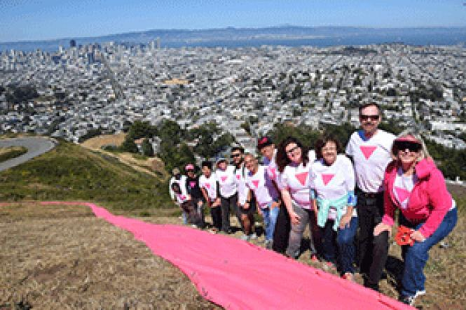 Patrick Carney, second from right, stands with volunteers<br>as they outline the pink triangle installation. Photo: Courtesy Patrick Carney
