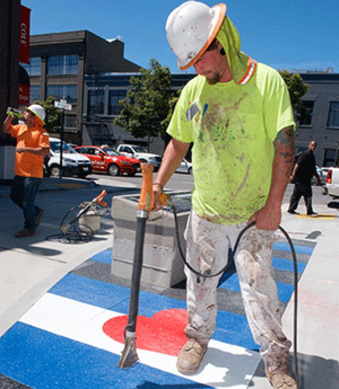 Construction worker Michael Bennett uses a torch to melt<br>thermo plastic leather flag colors into the sidewalk on Ringold Alley. Photo:<br>Jane Philomen Cleland