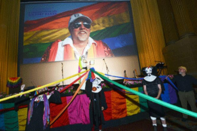 Sister Timothy Simplicity, on stage, reads a proclamation<br>designating Gilbert Baker as Sister Betsy Ross of the Sisters of Perpetual<br>Indulgence, while other Sisters hold rainbow ribbons strung down the aisles of<br>the Castro Theatre to open the celebration of life for Baker, the creator of<br>the rainbow flag. Photo: Rick Gerharter