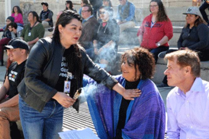 Maribel Martinez, left, wafts sage over the crowd at City<br>Hall during a recent transgender youth rally, as Santa Clara County Supervisor<br>Ken Yeager, right, looks on. Photo: Jo-Lynn Otto