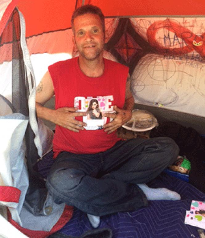 Keith Devill sits in his tent on Division Street. Photo:<br>Seth Hemmelgarn